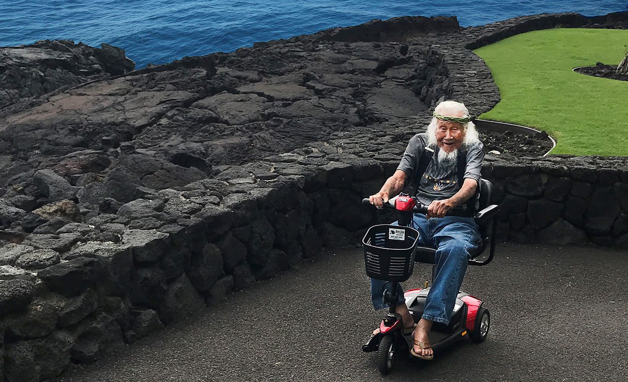 elderly Hawaiian man riding on a motorized scooter